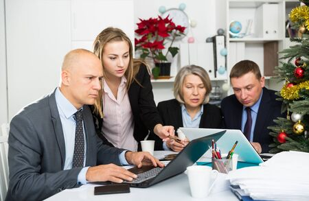 Confident businessman working with laptop on new business project with members of his team