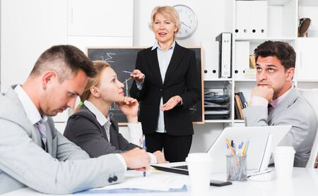 Businesswoman feeling angry to coworkers in office, pointing out their mistakes