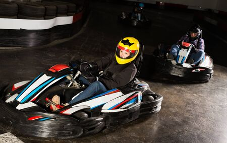 Young woman in helmet and other people driving cars for karting in sport club indoor Imagens