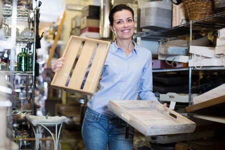 Femmina che tiene le scatole di legno per la sua casa in un moderno negozio di arredamento Archivio Fotografico