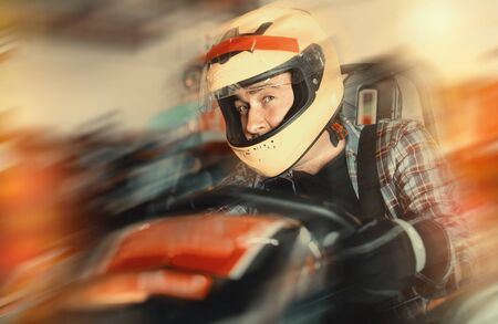 Glad smiling male in helmet and other people driving cars for karting in sport club indoor
