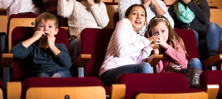 Scared of children enjoying scary film in in cinema house