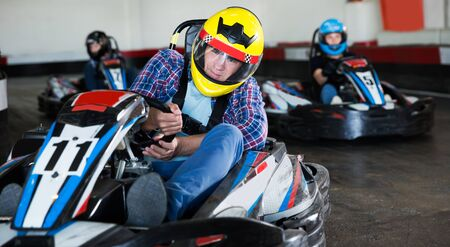 sportive concentrated  man and women competing on racing cars at kart circuit
