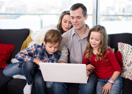 Happy family members enjoying movie on laptop together at home