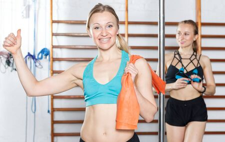 Portrait of happy sporty young woman standing near pylon in fitness gym Stock Photo