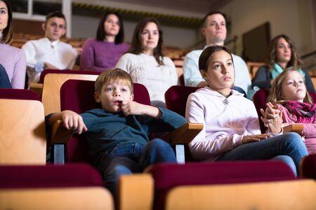 People audience attending movie night in cinema house