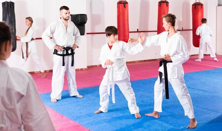 Pleasant kids in kimonos exercising techniques in pair during taekwondo class at gym Imagens - 133378894