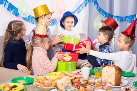 Smiling children presenting gifts to girl during birthday party