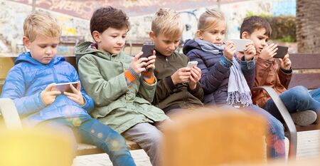 Group of children carried away with phone spending time together outdoors in autumn day Imagens - 133378900