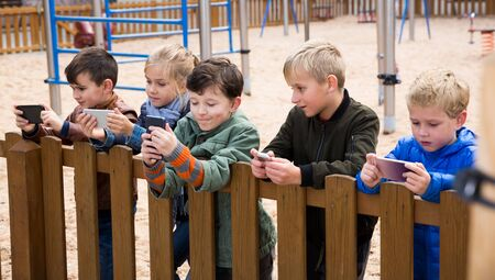 Interested kids playing with smartphones while standing near wooden fence on playground Imagens - 133378902