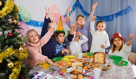 Happy pretty friendly  boys and girls behaving jokingly during friend's birthday party