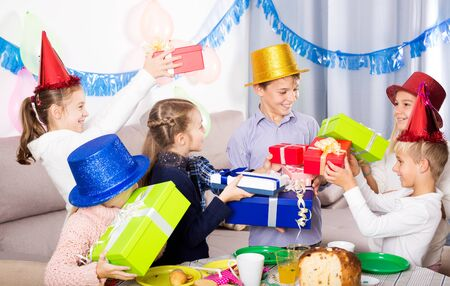 Smiling group of children presenting gifts to boy during birthday party