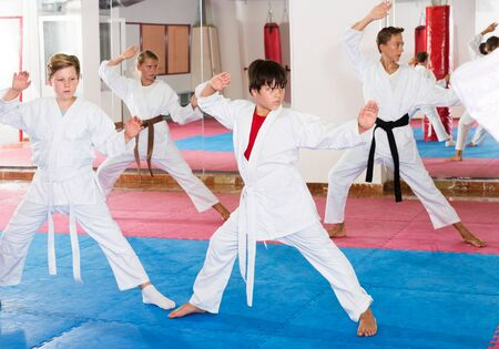 Teens wearing karate uniform practicing new moves in group at gym Imagens - 133378915