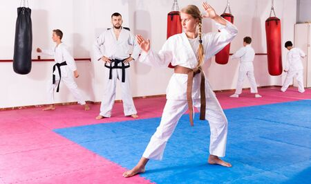Tween positive  girl mastering new taekwondo moves during group class with male coach Imagens - 133378918