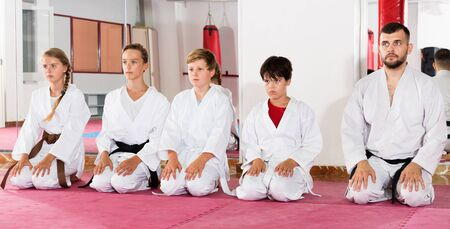 Group of diligent positive children dressed in kimonos sitting on floor at gym with young man trainer Imagens - 133378922