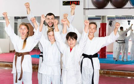 Group of emotional cheerful positive  kids with man trainer posing in gym after taekwondo workout Imagens - 133378924