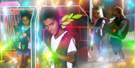 Positive african preteen boy with laser pistol playing laser tag with friends on dark labyrinth