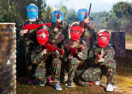 Friendly cheerful positive  group of children paintball players in camouflage posing with guns on paintball playing field outdoors 스톡 콘텐츠