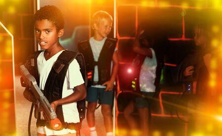 Confident tween mulatto boy standing with laser pistol in dark lasertag room during game with friends