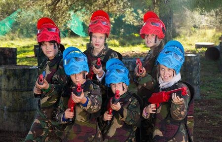 Portrait of boys and girls paintball players with marker guns ready for game outdoors 스톡 콘텐츠