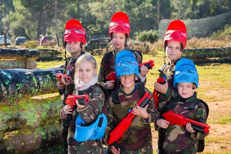 Portrait of group of kids paintball players with marker guns ready for game outdoors