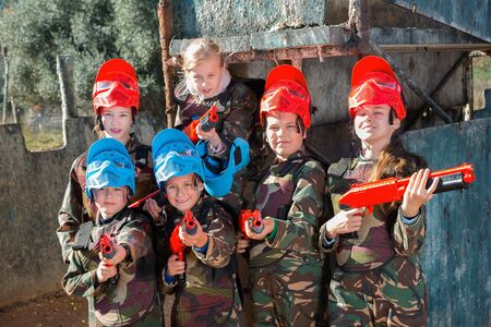 Friendly glad positive smiling  group of children paintball players in camouflage posing with guns on paintball playing field outdoors