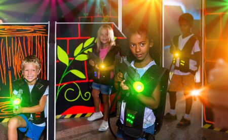Smiling african preteen girl with laser pistol playing laser tag with friends on dark labyrinth 스톡 콘텐츠