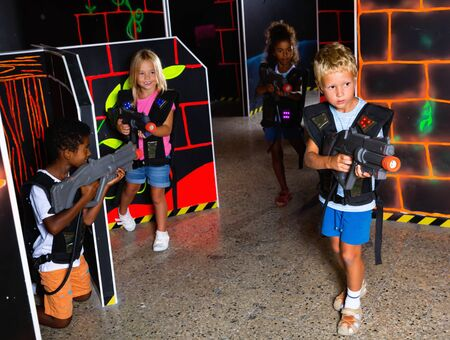 Multiracial team of  cheerful positive smiling tween kids aiming laser guns at other players during lasertag game in dark room