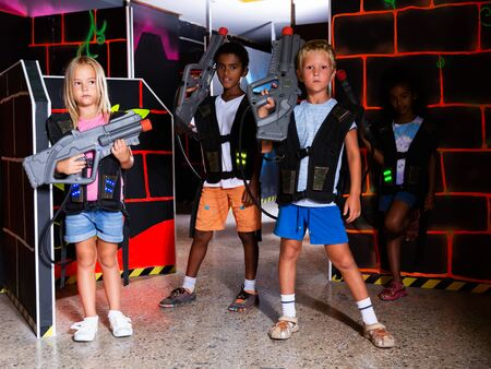 Group of glad pleasant teenagers with laser guns having fun on dark lasertag arena