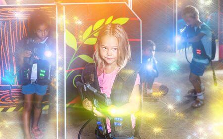 Tweenager girl with laser gun having fun on dark lasertag arena  Reklamní fotografie