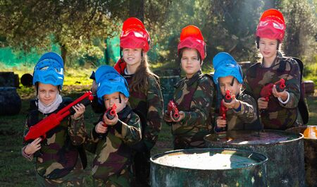 Friendly happy cheerful smiling group of children paintball players in camouflage posing with guns on paintball playing field outdoors 스톡 콘텐츠