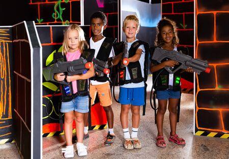 Multinational group of smiling tweenagers with laser guns having fun on dark lasertag arena
