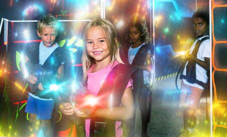 Smiling girl aiming laser gun at other players during lasertag game in dark room