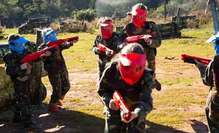 Teams of active concentrated kids facing on battlefield in outdoor paintball arena 스톡 콘텐츠