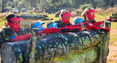 Team of boys and girls paintball players aiming and shooting with guns at opposing team outdoors. Focus on left boy