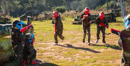 Two opposing teams of cheery kids shooting on paintball playing field outdoors