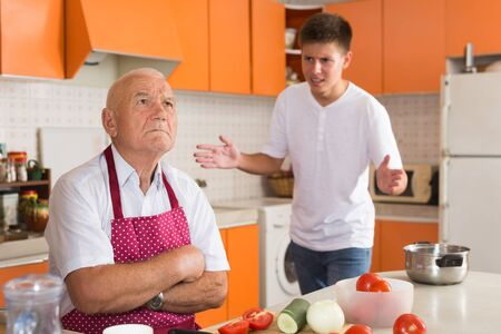 Offended elderly man sitting at kitchen table with disgruntled teenage grandson standing behind and reprimanding him Imagens