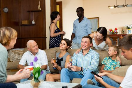 Happy large family having emotional conversation together at home Stock Photo