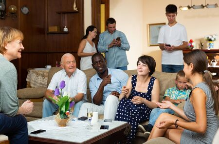 Three generations of happy multiethnic family lively talking together in cozy apartment