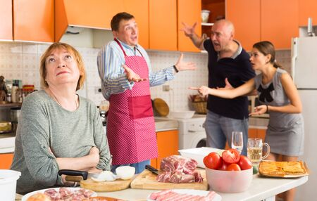Family quarreling during cooking dinner in kitchen