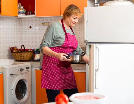 Smiling aged housewife putting pan in fridge in cozy home kitchen
