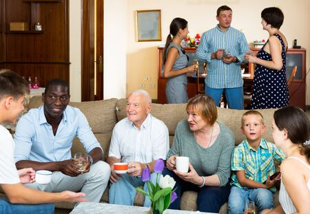 Big happy multiethnic family gathering in parental home, cheerfully talking together in living room