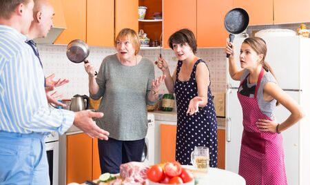 Two disgruntled women with elderly mother scolding their husbands in home kitchen. Family conflict
