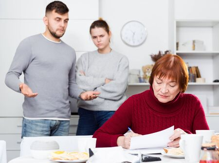 Frustrated senior woman looking at papers on background with discontented young couple