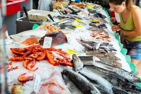 View of large assortment of fresh seafoods on icy showcase of fish store