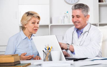 Mature woman visits doctor for survey of condition of health