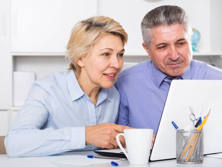 Colleagues discussing project and documents at office at table