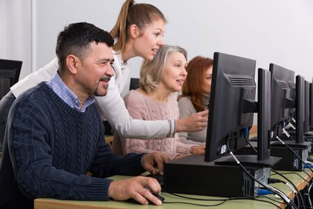 Young businesswoman helping to coworkers, pointing at computer monitor in office