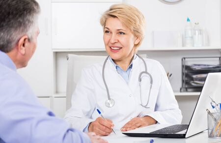 Doctor listens to mature patient and fills information card  Banque d'images