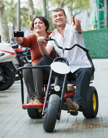 Agradable pareja adulta con bicicleta doble y cámara en vacaciones en las calles de la ciudad Foto de archivo